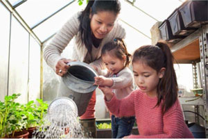 mom and two girls watering plants